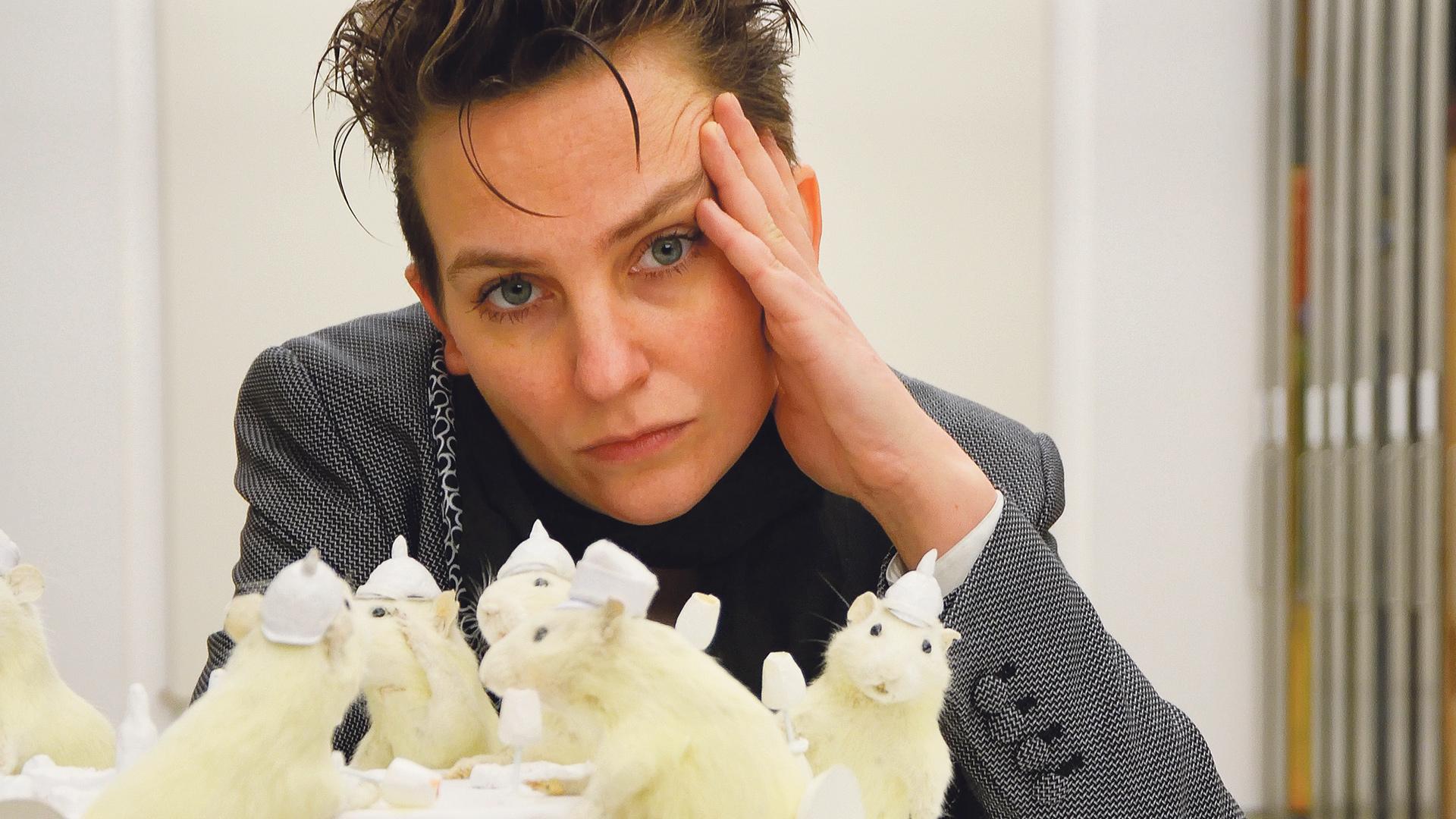 Frau stützt den Kopf mit dem Arm am Tisch vor ihr eine weiße Mäuseschar